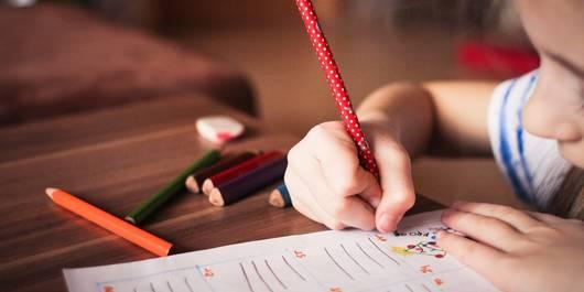 Ein Mädchen schreibt mit einem Stift auf ein Blatt Papier