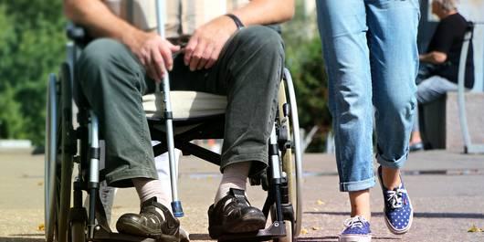 Ein Fußgänger und ein Mensch im Rollstuhl