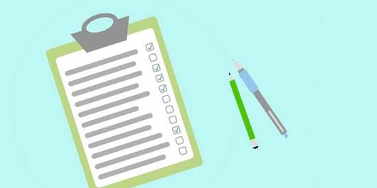 Klemmbrett mit Checkliste, danbene liegen Bleistift und Kugelschreiber